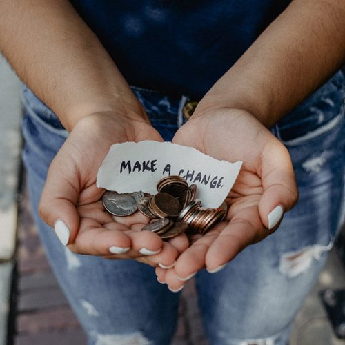 "hands holding change and sign that says ""make a change"""