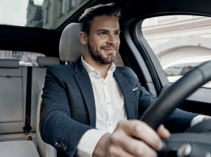 man in business attire driving a car