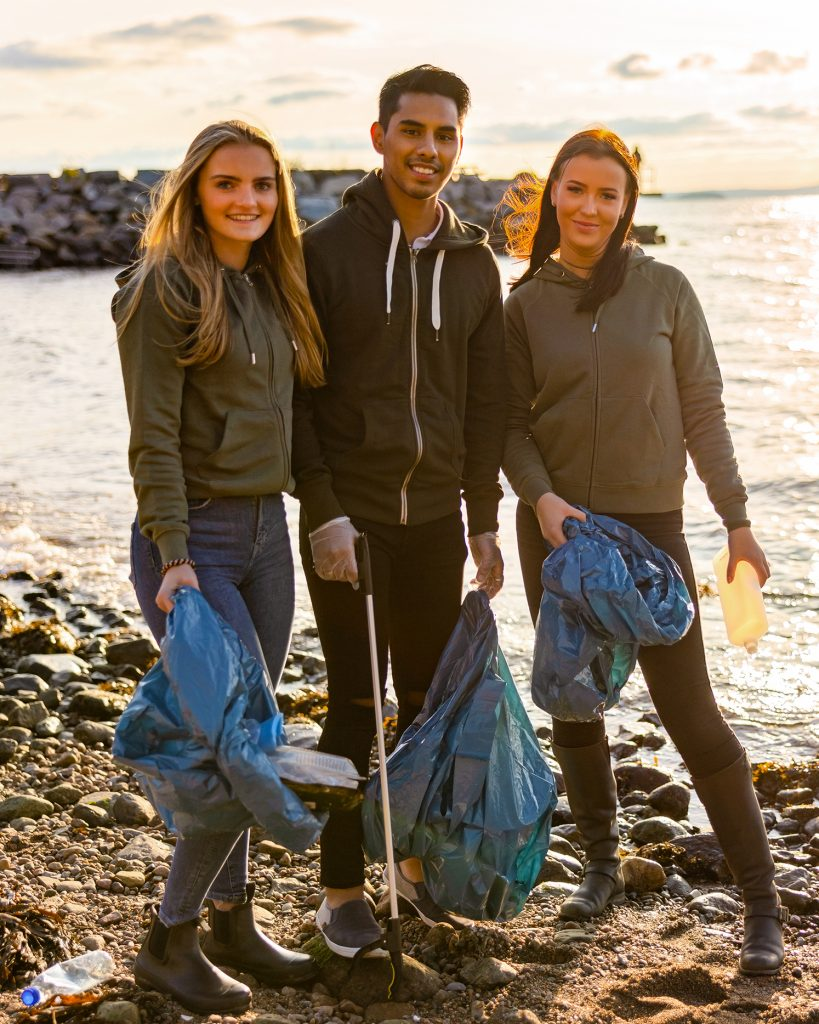 group of volunteers with trash bags cleaning a beach
