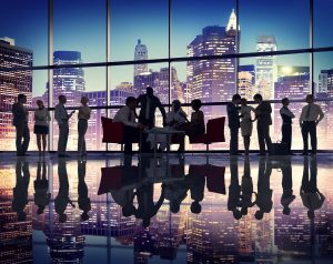 people in office setting with city skyline behind them