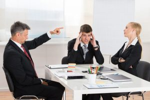 a man scolding a woman in office setting with upset coworker at desk