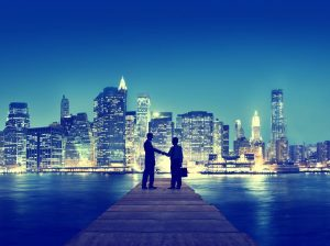 men shaking hands with city skyline behind them