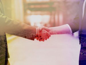 man and woman in business attire shake hands