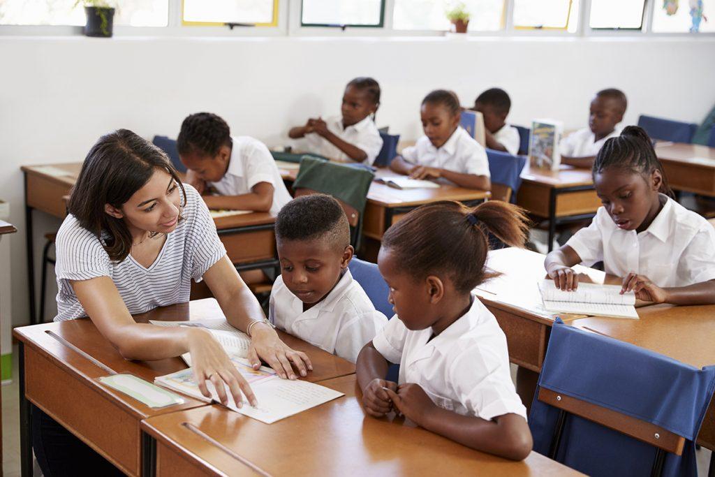 teacher helping students at their desks